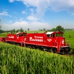 Railpower locomotives travel through fields and pastures.